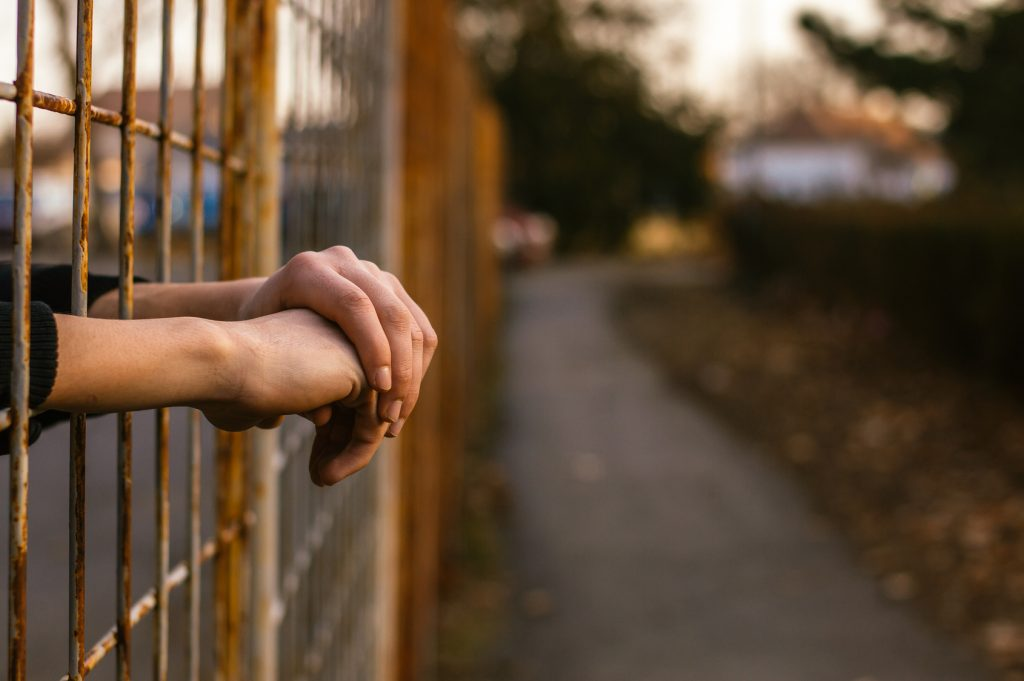 Atheist man's hands clasped together through a high fence.