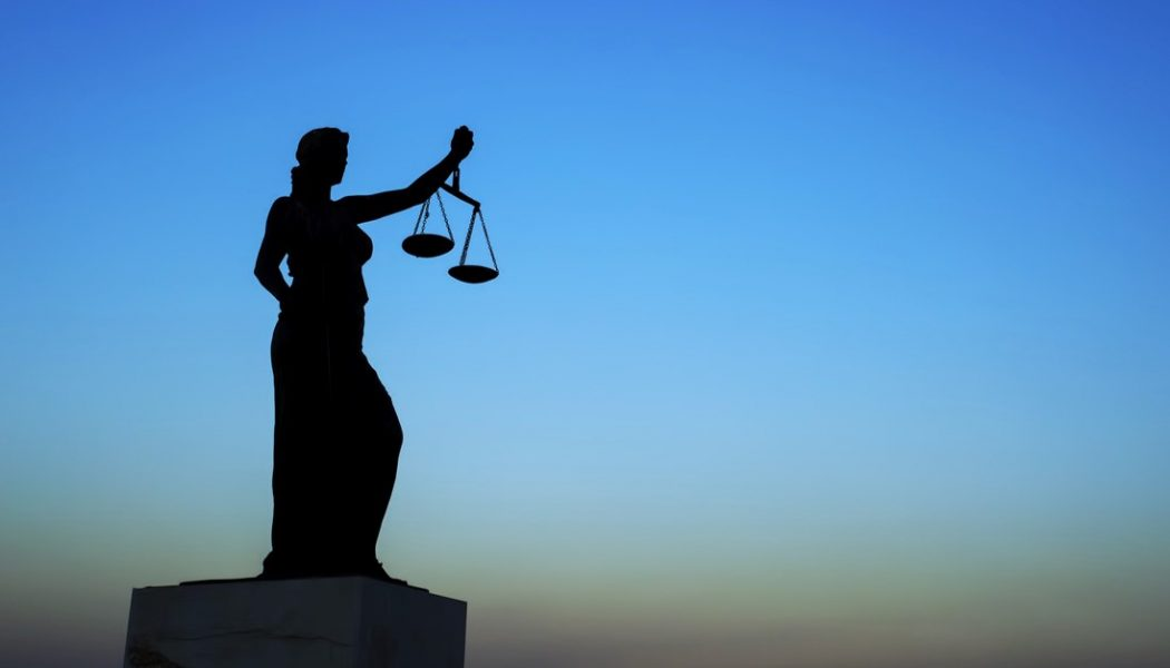 Blindfolded Lady Justice holding scales silhouetted against a dark sky