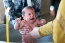 A baby as an unwilling participant in a Christening.