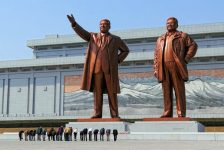 People bowing their heads to the Kim Il Sung statue in Pyongyang.