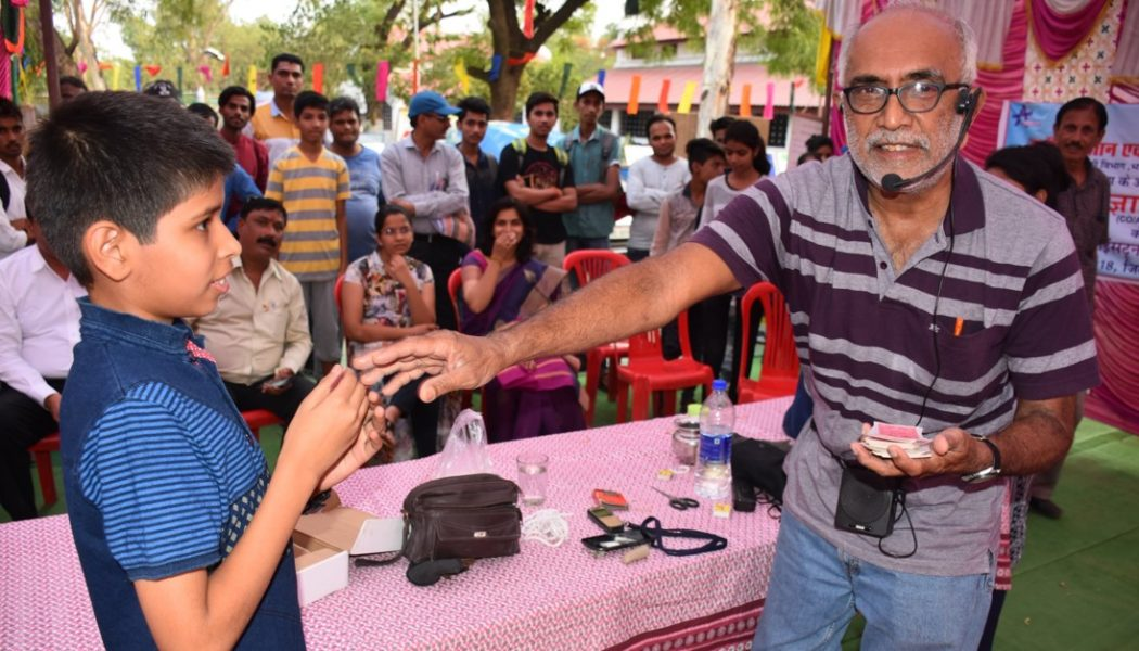 Narendra Nayak doing a card trick with a young volunteer