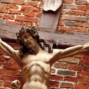 Wooden carving of Jesus crucifixion against a brick wall